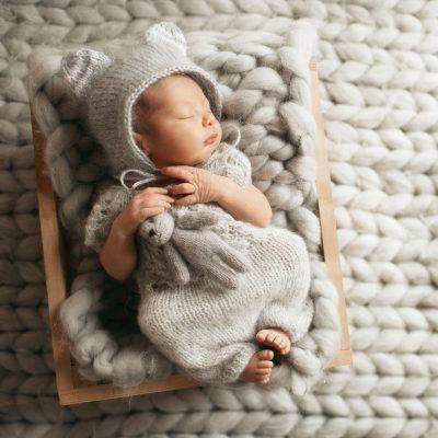 tiny-baby-in-grey-clothes-sleeps-on-woolen-blanket-CROP